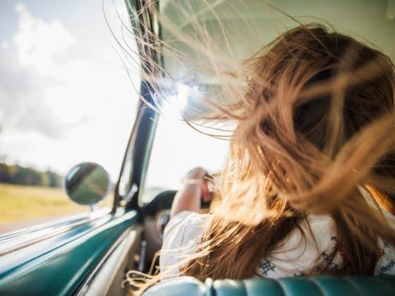 Frau am Steuer und der Fahrtwind bläst ihr ins Haar