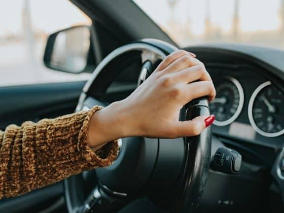 Frau im Auto mit Lenkrad in der Hand und roten Fingernägeln