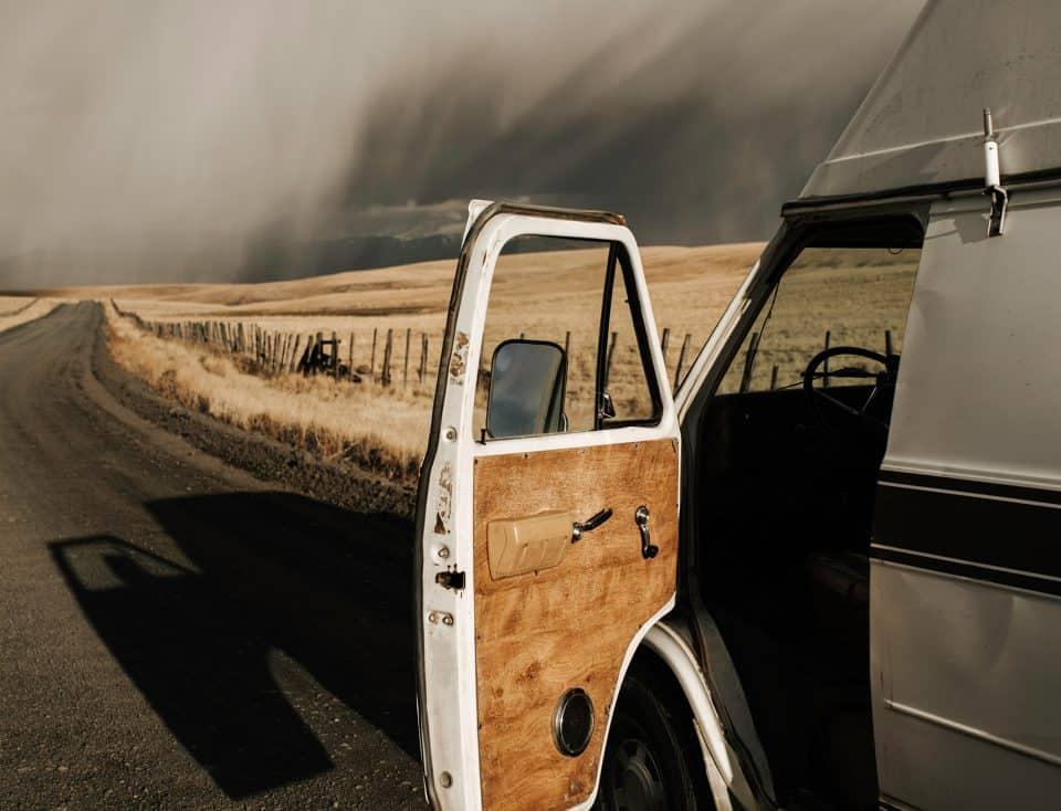 Alter Bus mit offener Autotür vor Landschaft