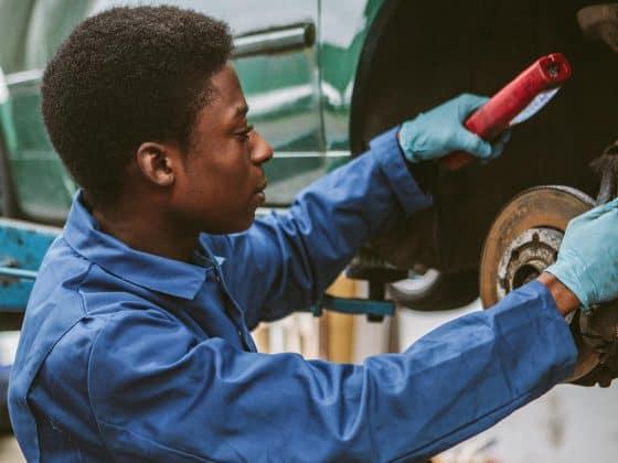 Mechanikerin schraubt an Auto in Werkstatt