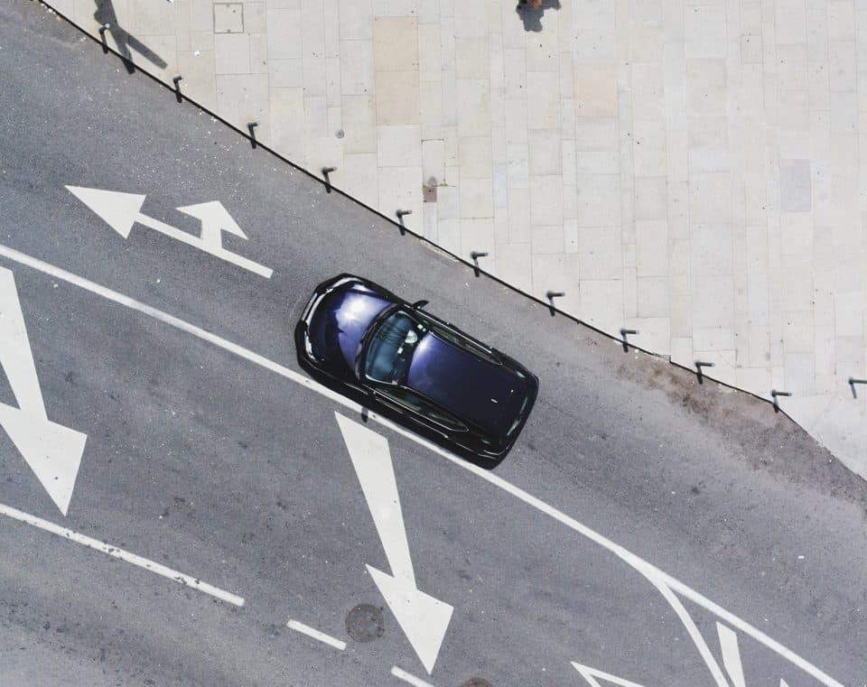 Auto auf Fahrbahn mit Straßenbodenmarkierungen