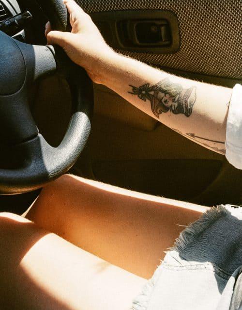 Tätowierte Frau im Auto mit kurzem Rock am Lenkrad